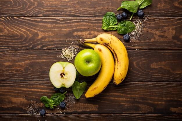 재료 fot 건강한 아침 식사 해독 녹색 스무디 그릇 바나나, 사과, 시금치 나무 표면에. 위에서보기