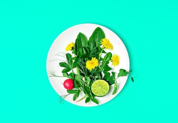 Ingredienti per una fresca insalata verde con denti di leone e fiori commestibili su un piatto