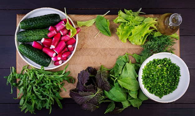 Ingredients for fresh salad of cucumbers, radishes and herbs