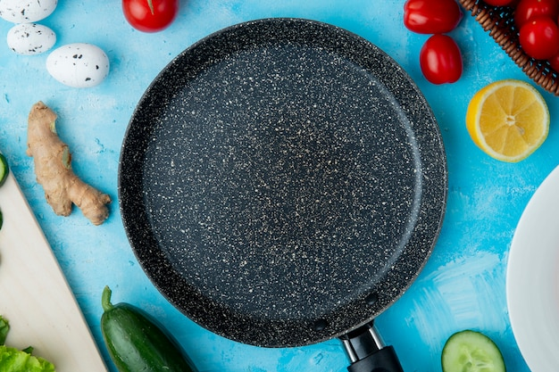 Ingredients and frying pan on blue surface