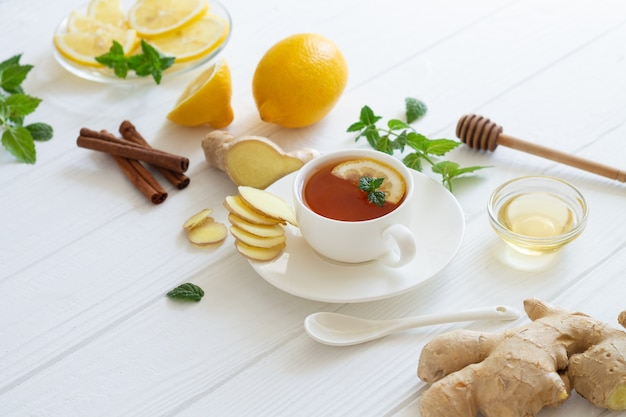 Ingredients for ginger tea with lemon, honey, mint, cinnamon on white table