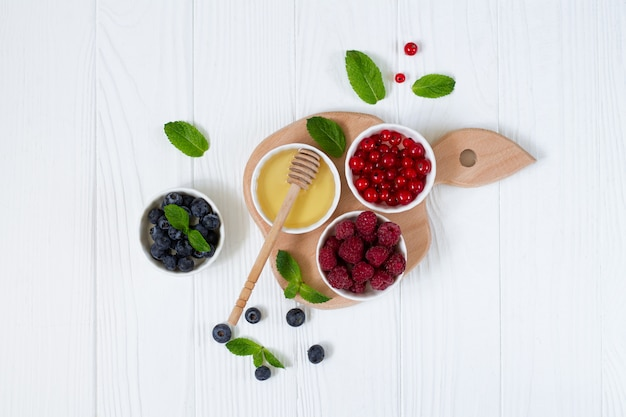 Ingredients for healthy breakfast - fresh rastberry, red currant, blueberry and honey top view on white wooden table. organic summer food for immunity booster concept