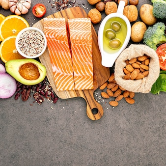 Ingredients for the healthy foods selection set up on dark stone background.