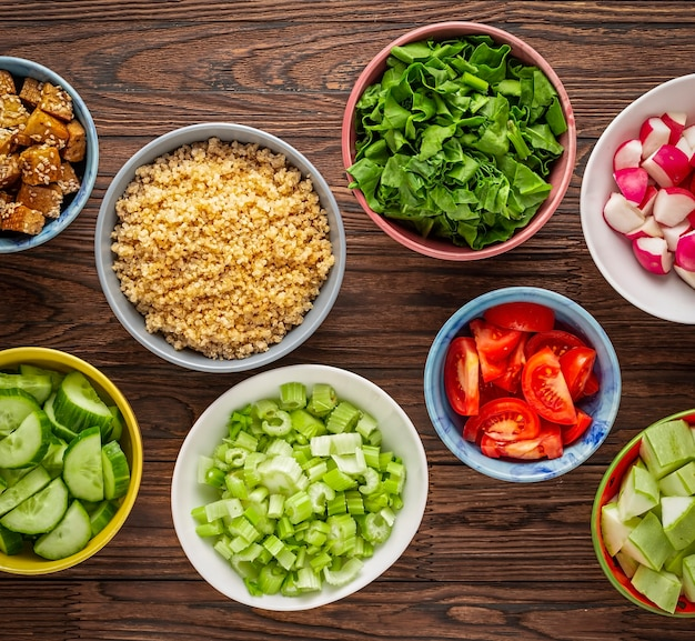 Ingredients of healthy nutrition in colorful bowls on a wooden table. quinoa, raw vegetables and fried tofu.