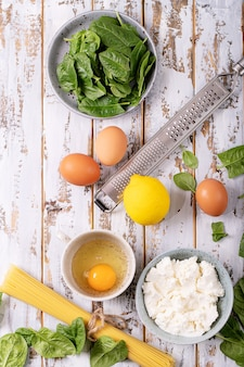 Ingredients for home made tagliatelle vegetarian egg pasta carbonara served with ricotta cheese, eggs and spinach over white wooden background.