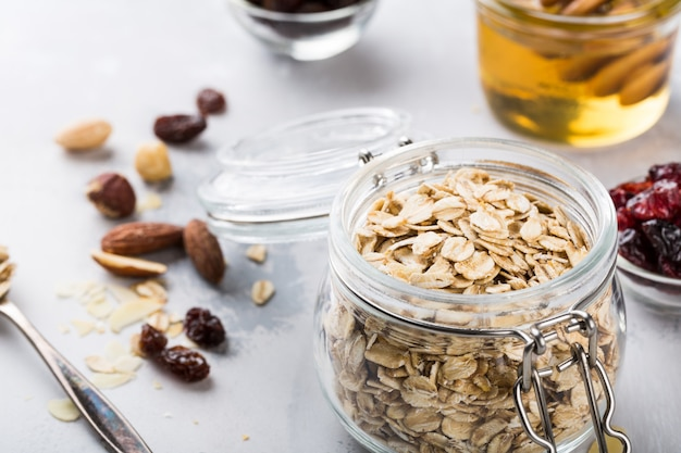 Ingredients for homemade oatmeal granola in glass jar.