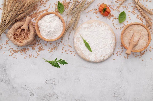 The ingredients for homemade pizza dough with wheat ears ,wheat flour and wheat grains set up on white concrete background.