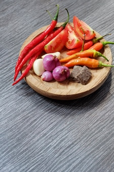 Ingredients of hot and spicy sambal placed on wooden plate at black wooden table shot vertically