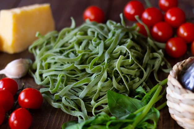 Ingredients for italian green pasta. wooden background.