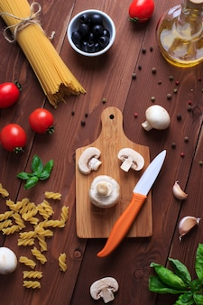 Ingredients for italian pasta and ceramic knife on brown wooden table