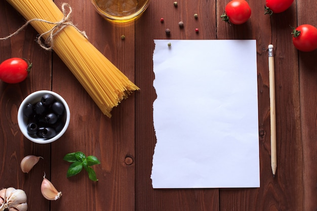 Ingredients for italian pasta on wooden table with paper for writing recipes.