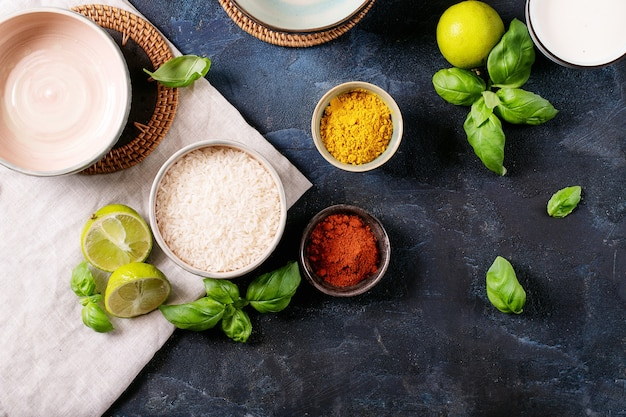 Ingredients for making a bowl of yellow curry served with basil, rice and limes