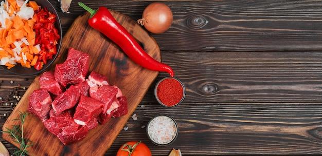 Ingredienti per preparare gulasch o spezzatino, spezzatino o gyuvech. vista dall'alto di carne di manzo cruda, erbe aromatiche, spezie, paprika, verdure sul tavolo di legno nero