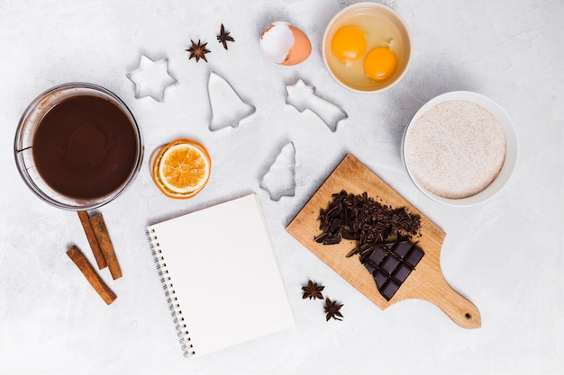 Ingredients of making the homemade cake with spiral notepad and pastry cutters on white background