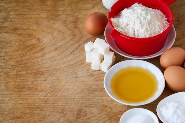 Ingredients for making pancakes on a wooden background
