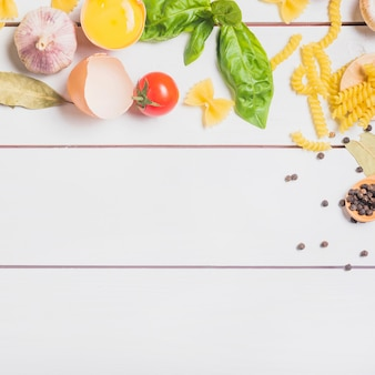 Ingredients for making raw homemade pasta on wooden plank