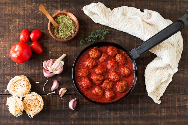 Ingredients and meatballs with tomato sauce on wooden background