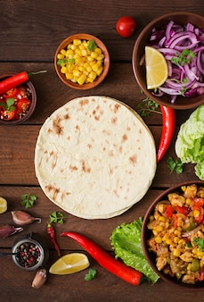 Ingredients for mexican tacos with meat, corn and olives on wooden background. top view