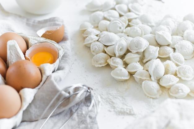 Ingredients for modeling homemade dumplings. eggs, milk, flour, salt, pepper, meat.