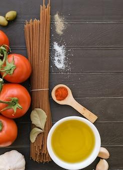 이탈리아 요리의 재료. 조리법에 대한 요리 배경. 다이어트 또는 비건 음식. 이탈리아 스파게티, 토마토, 마늘, 올리브 오일, 베이 잎의 상위 뷰.
