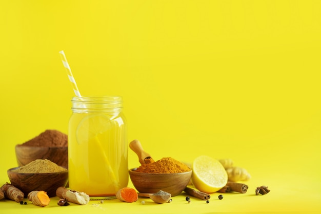 Ingredients for orange turmeric drink on yellow background. lemon water with ginger, curcuma, black pepper. vegan hot drink concept