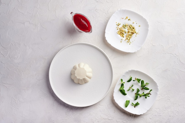 Ingredients for panna cotta with raspberry syrup, pistachios, berries and mint