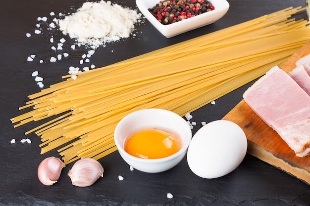 Ingredients for pasta carbonara on dark slate background. top view.