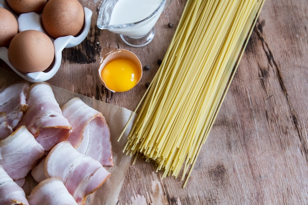 Ingredients for pasta carbonara with bacon, cheese, cream and yolk on wooden table