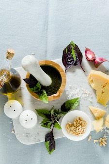 Ingredients for the preparation of italian basil purple pesto with cheese. on linen blue tablecloth