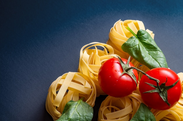 Ingredients for the preparation of italian pasta - spaghetti, fusilli, fettuccine, tomato.