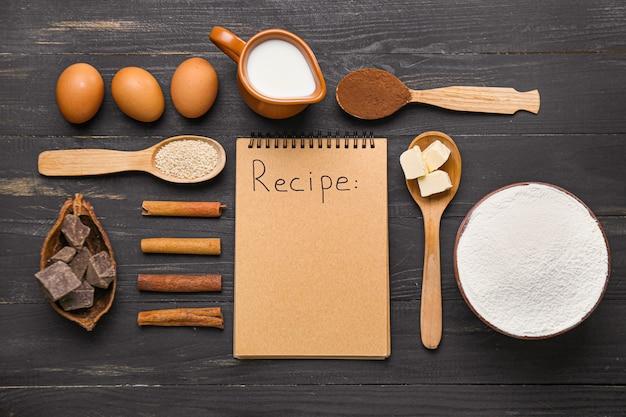 Ingredients for preparing bakery and notebook on dark wooden