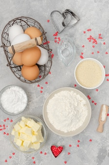 Ingredients for preparing of heart-shaped cookies for valentine's day.