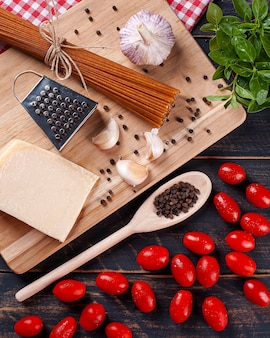 Ingredients for preparing italian food, whole spaghetti pasta, garlic, cherry tomatoes, parmesan cheese and basil
