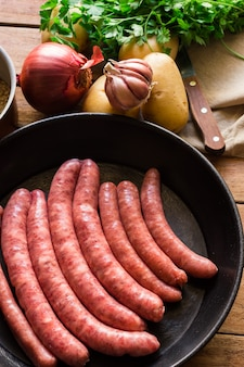 Ingredients for preparing meal, raw uncooked sausages in iron cast pan, potatoes, onion
