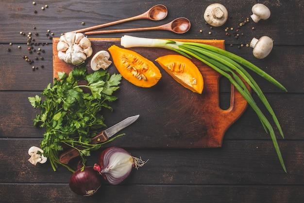 Ingredients for pumpkin soup on dark wooden background, top view.