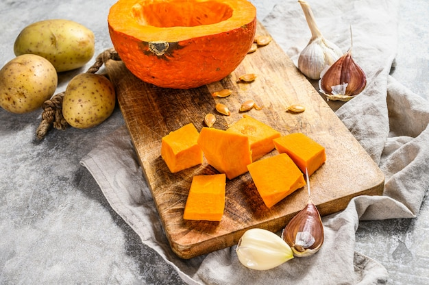 Ingredients for pumpkin soup. gray wall. chopped pumpkin on rustic cutting board. tasty and healthy food. vegan food