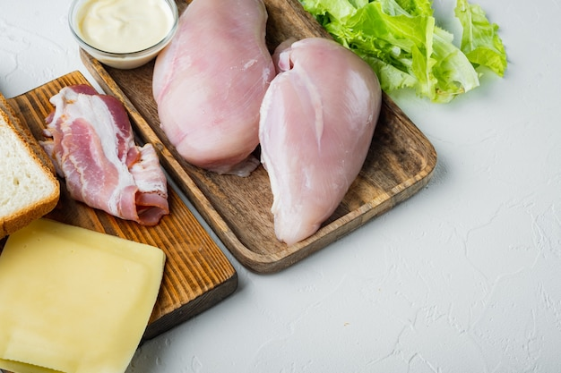 Ingredients for sandwich, bacon, cheese, tomato, chicken meat, lettuce, sauce