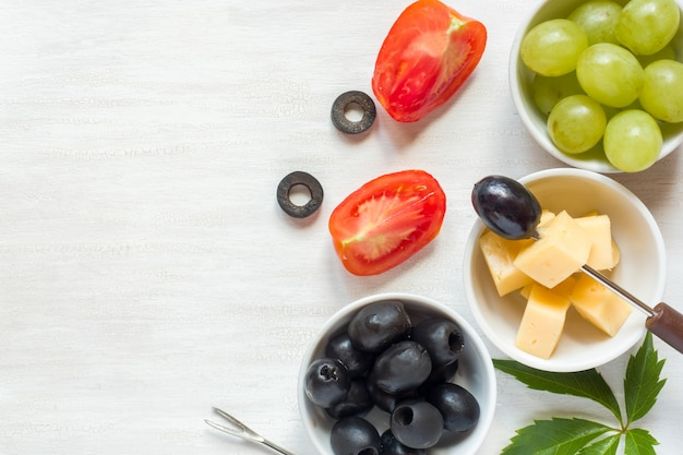 Ingredients for snacks, cheese with olives and tomato, grape on a white table