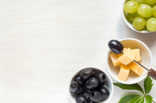 Ingredients for snacks, cheese with olives on a white table