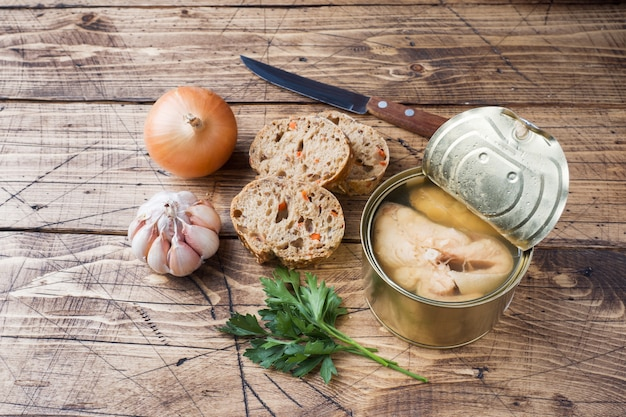 Ingredients for soup jar with pink salmon fish, pieces of bread, onion and garlic with greens on wooden background.