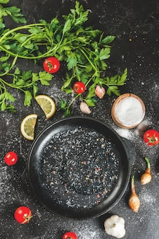 Ingredients and spices for cooking dinner: tomatoes, greens (parsley), salt, pepper, onions, shallots, garlic. with a frying pan, on a black concrete table, vertical, copy space