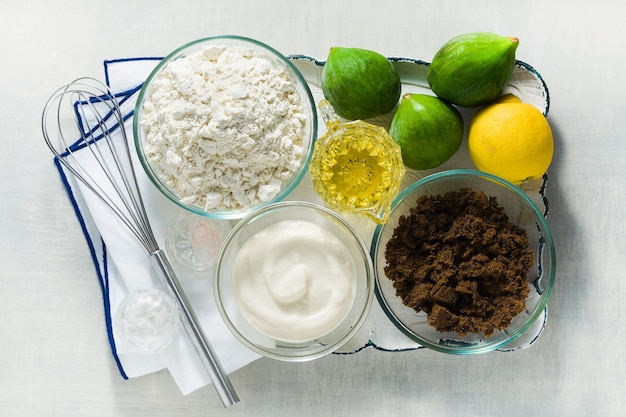Ingredients for sweet baked figs on a tray. flour, muscovado sugar, yogurt and lemon