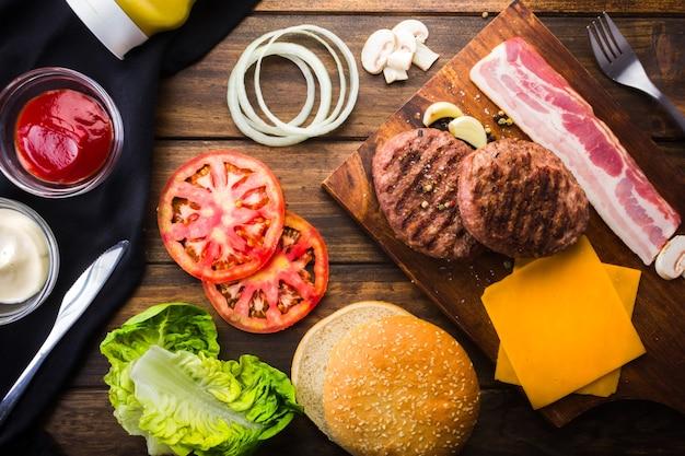 집에서 햄버거를 만들기 위한 재료, 빵, 고기, 토마토, 양상추 베이컨, 치즈.