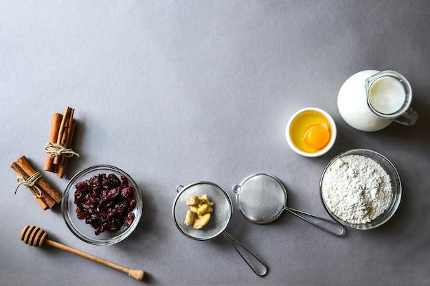 灰色の背景にパンケーキやクリスマスジンジャーブレッドを作るための材料。テキスト用のスペースをコピーします。ベーキングの背景レシピ
