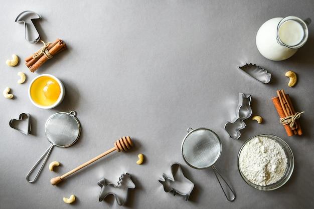 灰色の背景にパンケーキやクリスマスジンジャーブレッドを作るための材料。テキスト用のスペースをコピーします。ベーキングレシピ