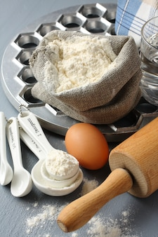 Ingredients and tools to make russian pelmeni on gray background