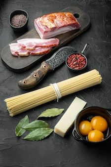 Ingredients for traditional italian pasta alla carbonara. uncooked spaghetti pancetta bacon