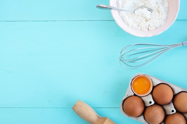 Ingredients and utensils for baking on wooden table