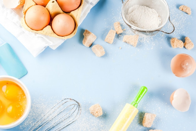 Ingredients and utensils for cooking baking egg, flour, sugar, whisk, rolling pin, on blue background, top view