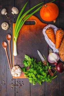 Ingredients for vegetable vegetarian soup on dark wooden background, top view.